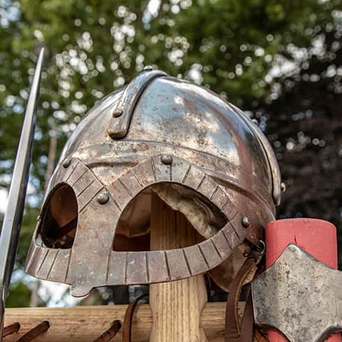The image shows a replica Viking helmet made from steel that has extra eye protection. Based on a find from Gjermundbu Norway