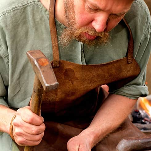 The image shows a bearded blacksmith forging a socket for an arrowhead, beating hte hot metal with his hammer.
