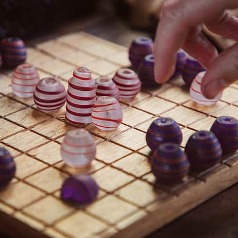 The image shows a replica Hnefatafl set, with the pieces made from glass. The player is moving a piece. Based ona  find from Birka, Sweden.