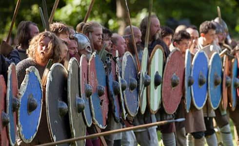 The image shows a long line of warriors forming the shield wall with their weapons at the reading and preparing to march against their enemy.