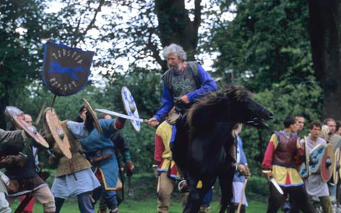 A action shot from a viking battle reenactment showing a horse rider attacking a shield wall.